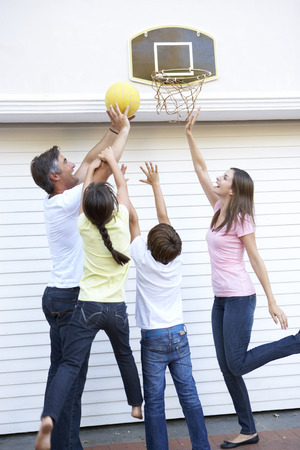 family playing: Family Playing Basketball Outside Garage Stock Photo
