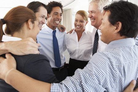 man woman hugging: Group Of Businesspeople Bonding In Circle At Company Seminar