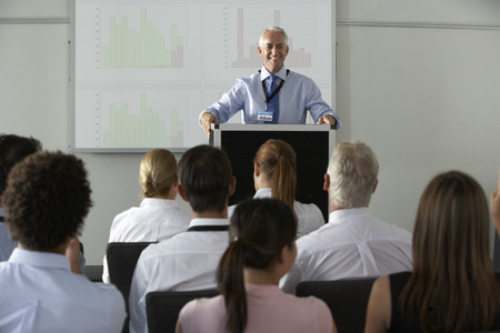 conference audience: Middle Aged Businessman Delivering Presentation At Conference