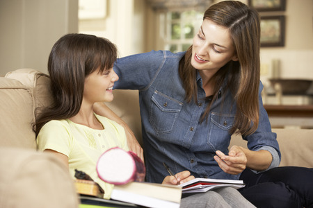 mum and daughter: Mother Helping Daughter With Homework Sitting On Sofa At Home