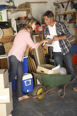 yard sale: Couple Clearing Garage For Yard Sale Stock Photo