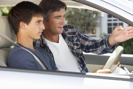 learning: Father Teaching Teenage Son To Drive