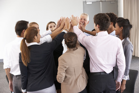 joining hands: Group Of Businesspeople Joining Hands In Circle At Company Seminar Stock Photo