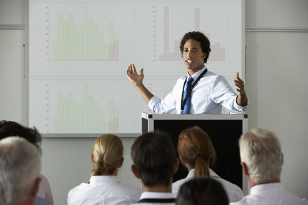 Young Businessman Delivering Presentation At Conference Stock Photo