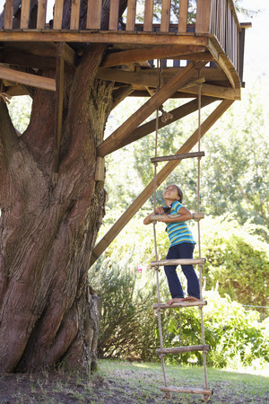 rope ladder: Young Girl Climbing Rope Ladder To Treehouse