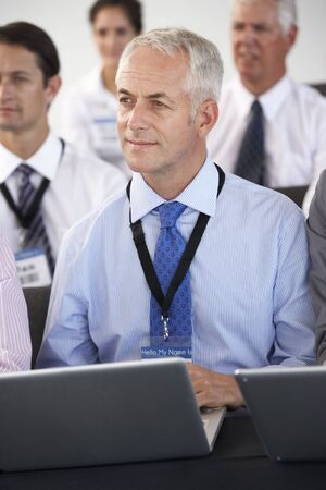 delegar: Delegado Hombre Escucha La Presentación En Realización de conferencias Notas en la computadora portátil Foto de archivo