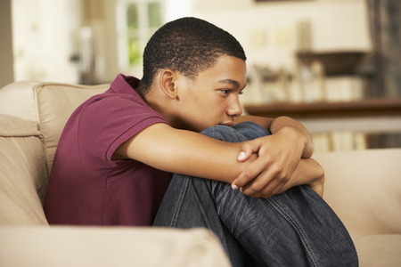 boy sitting: Unhappy Teenage Boy Sitting On Sofa At Home