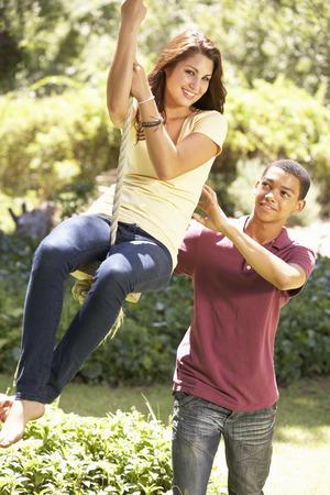 pareja adolescente: Pares adolescentes que se divierten en Columpio de cuerda Foto de archivo