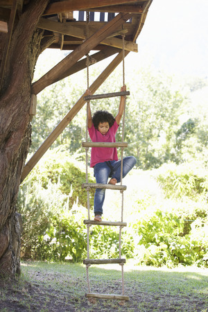 rope ladder: Young Boy Climbing Rope Ladder To Treehouse