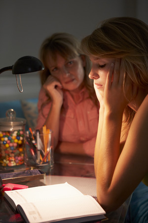 teenage girl: Unhappy Teenage Girl Looking At Diary In Bedroom At Night