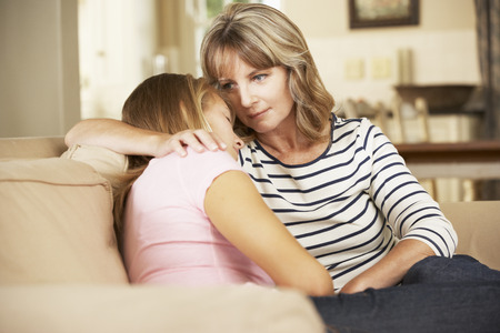 Mother Comforting Teenage Daughter Sitting On Sofa At Home Foto de archivo