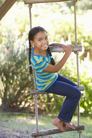 niños felices: Chica joven Escalada Escalera de cuerda Para Treehouse