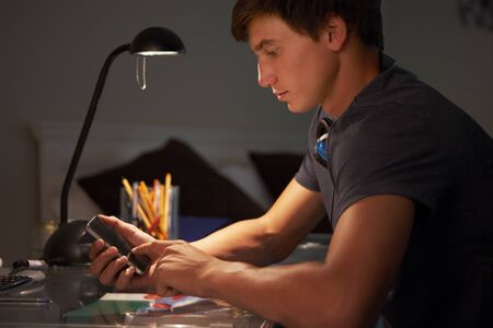 whilst: Teenage Boy Texting On Phone Whilst Studying At Desk In Bedroom In Evening Stock Photo