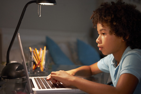 Young Boy Studying At Desk In Bedroom In Evening On Laptop