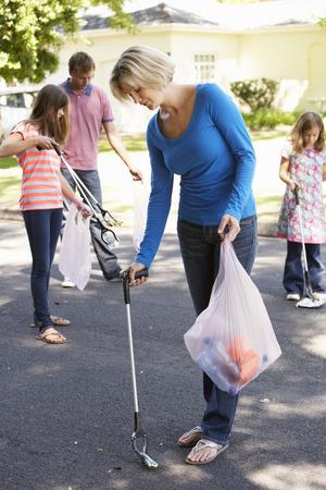personas ayudando: Familia que toma la litera en los suburbios de la calle Foto de archivo
