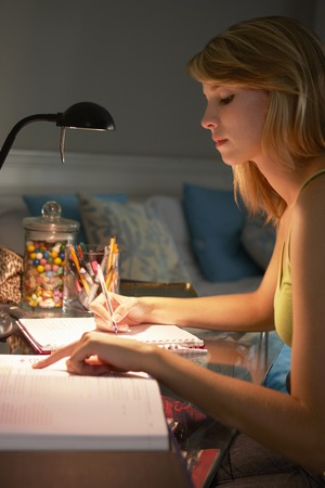 late teens: Teenage Girl Studying At Desk In Bedroom In Evening On Laptop Stock Photo