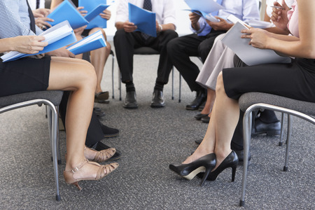 businesswoman legs: Detail Of Businesspeople Seated In Circle At Company Seminar Stock Photo