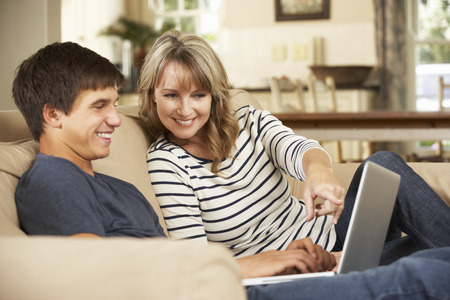 two parents: Mother With Teenage Son Sitting On Sofa At Home Using Laptop