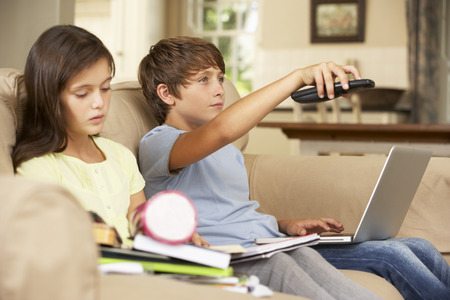distracted: Two Children Distracted By Television Whilst trying To Do With Homework