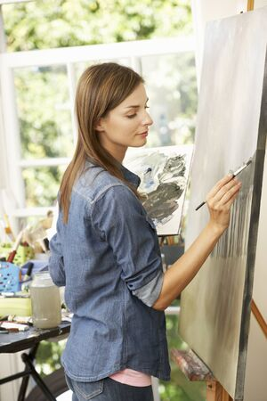 artist painting: Female Artist Working On Painting In Studio