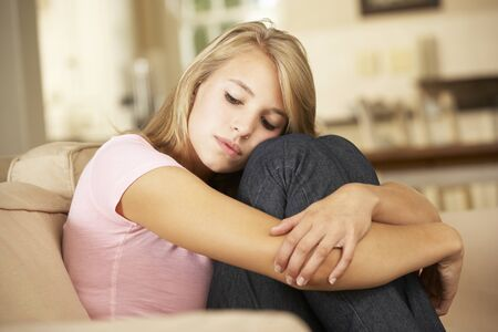 one teenager: Unhappy Teenage Girl Sitting On Sofa At Home