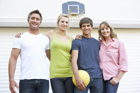 garage: Portrait Of Teenage Family Playing Basketball Outside Garage