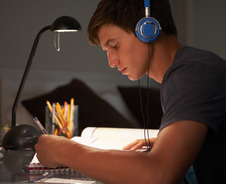 teenage male: Teenage Boy Listening to Music Whilst Studying At Desk In Bedroom In Evening Stock Photo