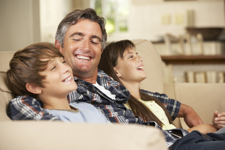 sofa television: Father And Two Children Sitting On Sofa At Home Watching TV Together Stock Photo