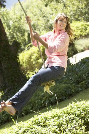 femmes souriantes: Femme Middle Aged Having Fun Sur Corde pour se balancer