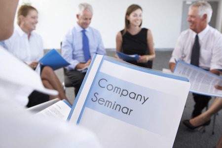 mixed age range: Detail Of Businesspeople Seated In Circle At Company Seminar Stock Photo