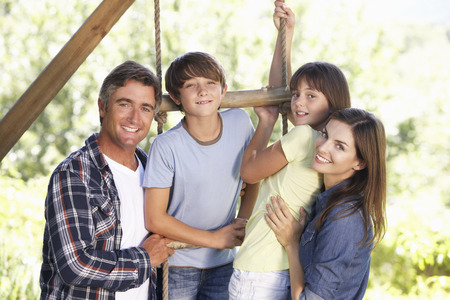 about age: Family In Garden By Treehouse Stock Photo