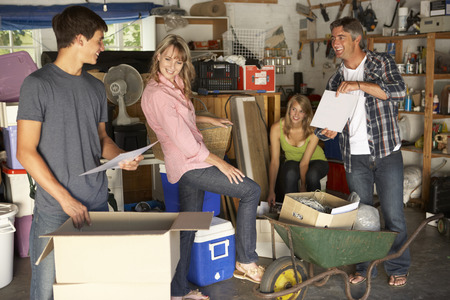 junk yard: Teenage Family Clearing Garage For Yard Sale