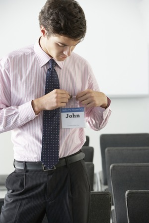 tage: Male Delegate Attaching Name Badge At Conference