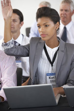 delegate: Female Delegate Listening To Presentation At Conference Making Notes On Laptop Stock Photo