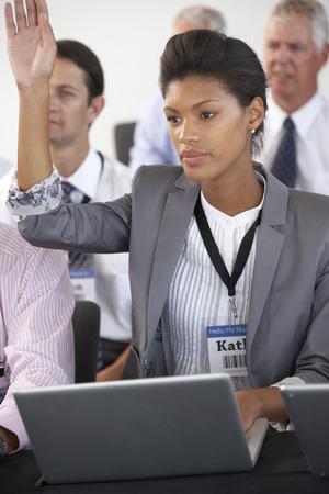 delegar: Mujer Delegado Escucha La Presentación En Realización de conferencias Notas en la computadora portátil