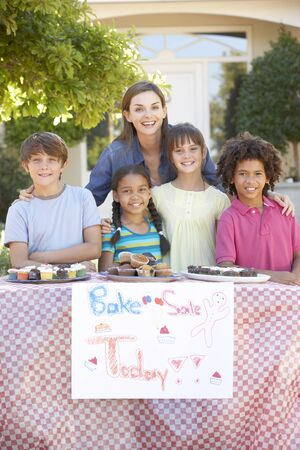 bake sale sign: Group Of Children Holding Bake Sale With Mother Stock Photo
