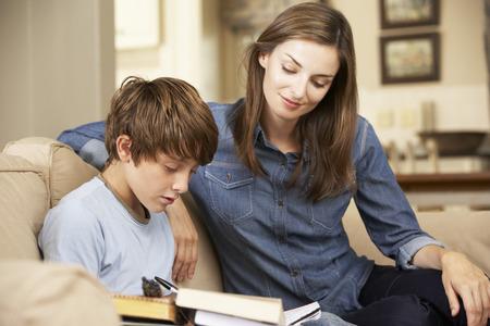 Moeder die Zoon met huiswerk zittend op de bank thuis