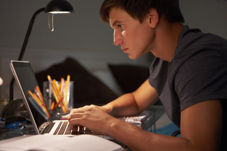 late teens: Teenage Boy Studying At Desk In Bedroom In Evening On Laptop Stock Photo