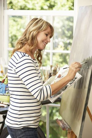 middle aged woman: Female Artist Working On Painting In Studio