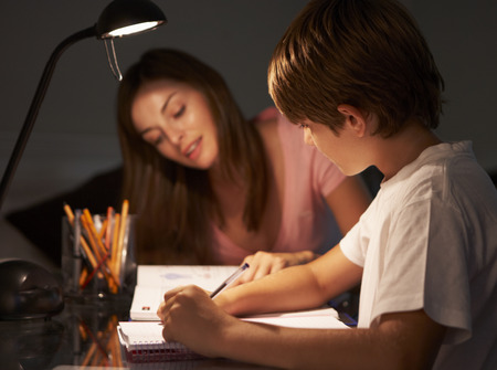 Teenage Sister Helping Younger Brother With Studies At Desk In Bedroom In Evening
