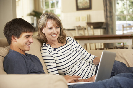 son's: Mother With Teenage Son Sitting On Sofa At Home Using Laptop