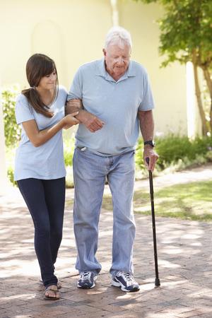 Tiener Kleindochter Helpen Grootvader Out On Walk Stockfoto