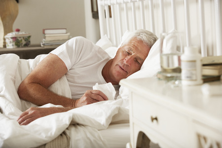chory: Chory starszy mężczyzna w łóżku w domu Zdjęcie Seryjne