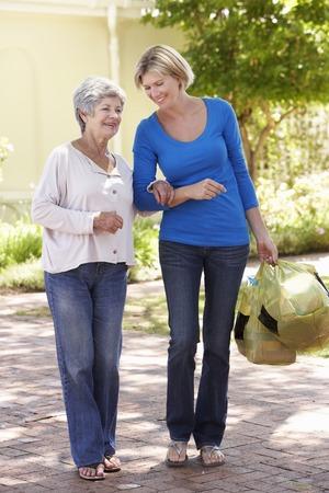 ayudando: Ayuda de la mujer mayor Mujer Con Compras Foto de archivo