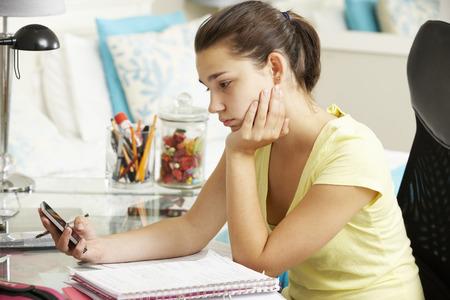 chicas adolescentes: Infeliz Adolescente Estudiando En El Escritorio En La Habitacion Mirando a Teléfono Móvil