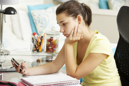 homework: Unhappy Teenage Girl Studying At Desk In Bedroom Looking At Mobile Phone