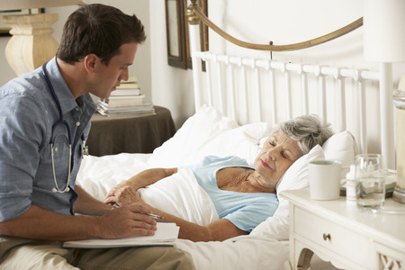 seniors: Doctor Talking With Senior Female Patient In Bed At Home Stock Photo