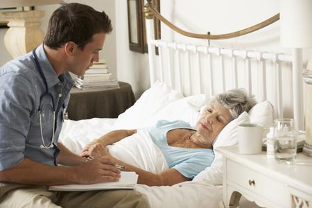 seniors: El doctor habla con el paciente de sexo femenino mayor en la cama en el pa�s