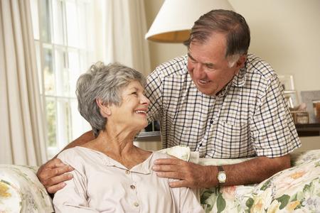 ancianos felices: Pares mayores jubilados que se sientan en el sofá en el país junto