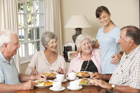 comunidad: Grupo de Pares mayores que disfrutan de la comida junto en atención domiciliaria con un adolescente ayudante